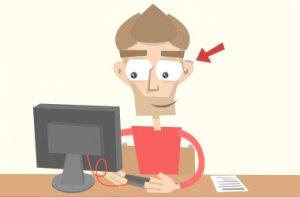 Tom sitzt an seinem Schreibtisch. Er arbeitet mit einer Hörbeeinträchtigung.