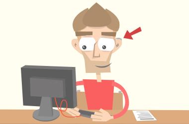 Tom sitzt an seinem Schreib-Tisch. Er arbeitet mit einer Hör-Beeinträchtigung.